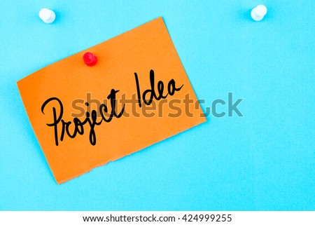 Project Idea written on orange paper note pinned on cork board with white thumbtack, copy space available