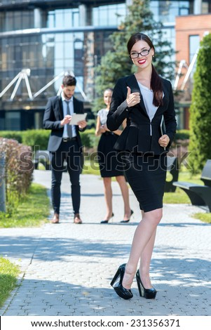 Project is done successfully. Young smiling businesswoman is showing that project is well done. Two her confident business colleagues are standing on the background and working with tablet - stock photo