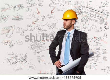 Project manager in a suit with hard yellow helmet over desk with drawnings.