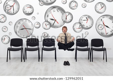 Project manager juggling with deadlines - surrounded by distorted wall clock bubbles - stock photo