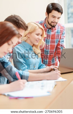 Project study.  Young initiative students use laptop in class doing their task - stock photo