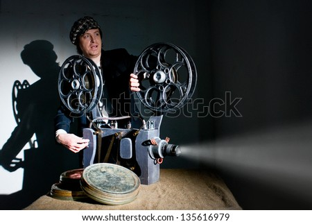 Projectionist and film projector with film - stock photo