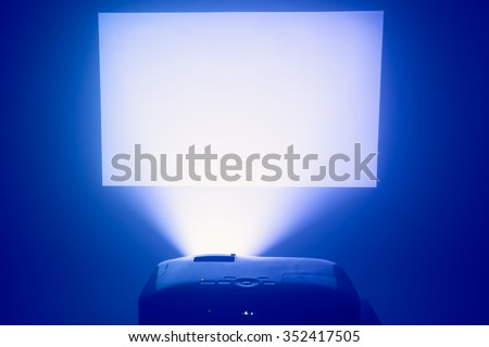 projector in action with illuminated screen - stock photo
