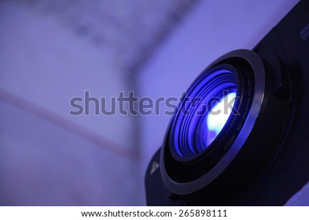 projector lens with beam of light active  - stock photo
