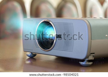Projector on office table ready for presentation with chairs in background - stock photo
