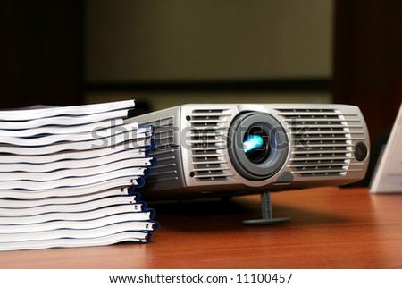 Projector with pile of books on the table - stock photo