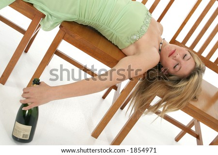 Prom teen passed out with empty bottle of champagne. - stock photo