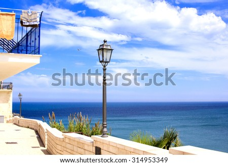 Promenade by the seaside in Vieste town, Puglia, Italy. Picture features horizon over sea with beautiful cloudscape and some city installations on the foreground : lamppost, stone fence, balcony. - stock photo