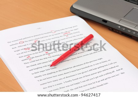 Proofreading a Manuscript beside Laptop - stock photo