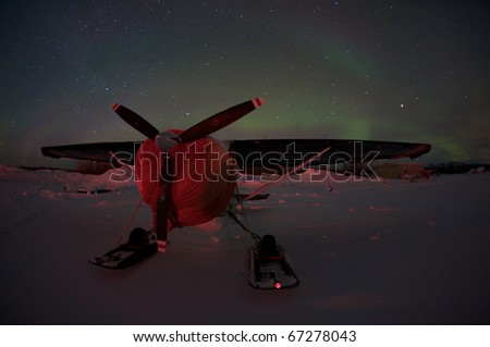 Prop driven plane parked in snow under the northern lights. - stock photo