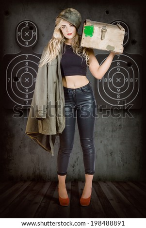 Propaganda style military portrait of a bomb shell blond army pinup girl carrying box of bullets at army shooting range with body target practice background. Bullet proof - stock photo