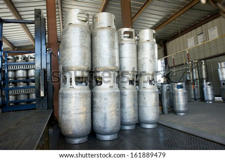 Propane cylinders in a warehouse await transport on a loading dock. - stock photo