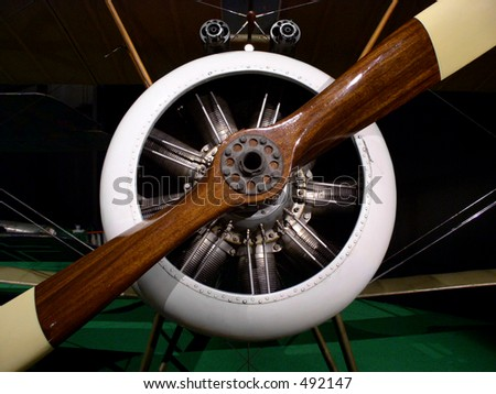 Propeller aircraft engine on a WWI biplane.  Rotary piston engine drives wooden propeller on this vintage aircraft. - stock photo