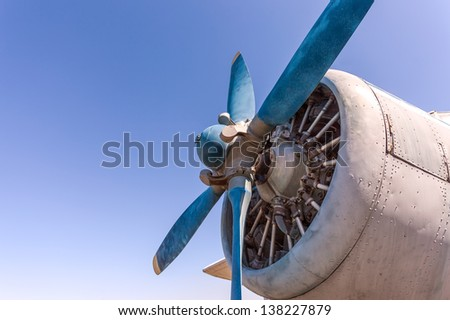 Propeller and engine of old airplane against blue sky - stock photo
