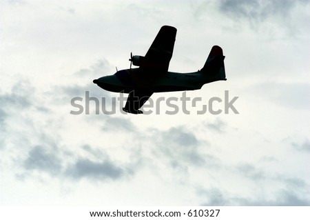 Propeller driven airplane silhouetted against an overcast sky