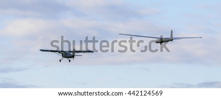 Propeller plane towing glider in a cloudy sky