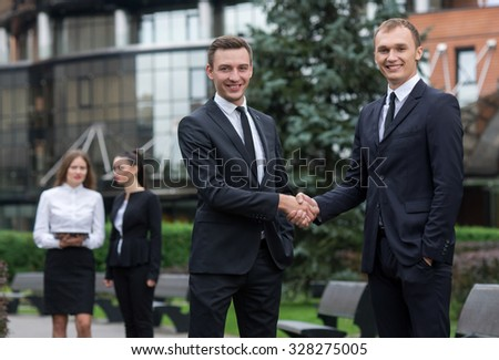 Proper business agreement. Group of confident and motivated business partners at work, both are shaking hands. Both men are wearing formal suits. Outdoor business concept