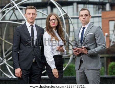 Proper business agreement. Group of confident and motivated business partners at work, discussing issues of business project. All are wearing formal suits. Outdoor business concept - stock photo