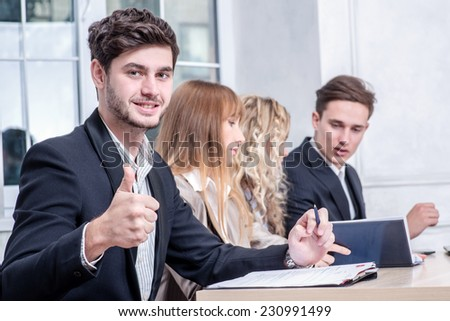 Proper business. Smiling businessman sitting at the table and happily shows thumbs up to the camera while his colleague businessmen talking in the background - stock photo