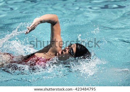 Proper swimming stroke with elbow high up - freestyle swimmer in action. Toned image, high speed - stock photo