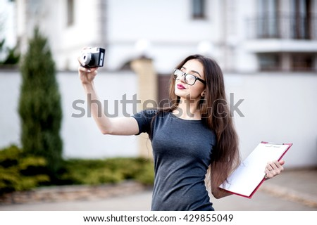 Property businesswoman, bank and happy people concept - beautiful successfull woman in sunglasses make photo on camera while walking outdoor. City business woman working. Stylish purse. - stock photo
