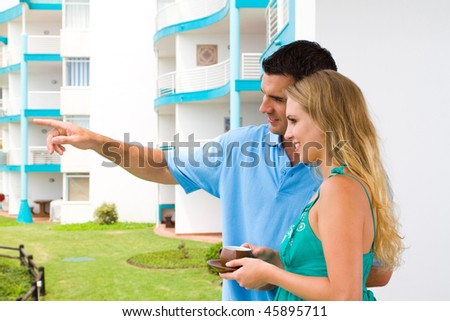 property investment - young couple drinking coffee on new home balcony - stock photo