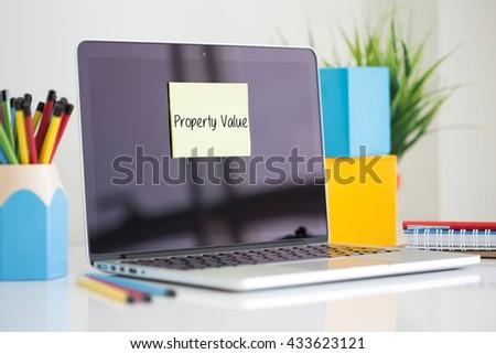 Property Value sticky note pasted on the laptop - stock photo