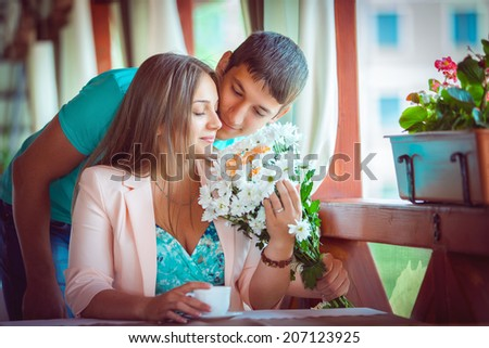 Proposal. Young couple in an open-air cafe - stock photo