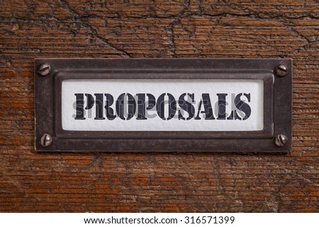 proposals  - file cabinet label, bronze holder against grunge and scratched wood