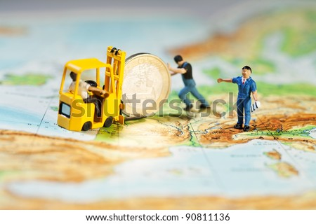 Propping Up The Euro. Team of tiny miniature figurines propping up the Euro and loading it on to a forklift, map of Europe concept. - stock photo