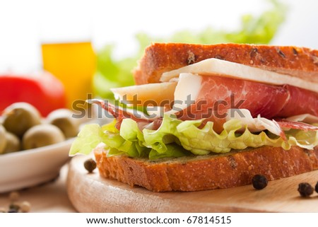 Prosciutto and cheese sandwich with olives and lettuce.
