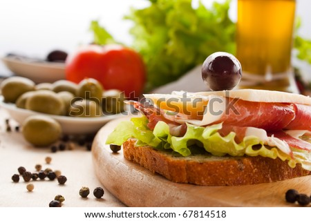 Prosciutto and cheese sandwich with olives and lettuce.Focus is on the cheese. Shallow depth of field. - stock photo