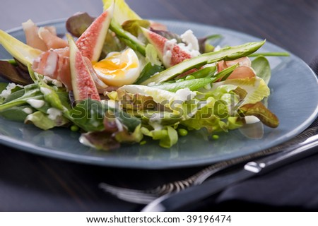 prosciutto and fig salad with aioli served on a plate on a dark wood table top and cutlery on the side