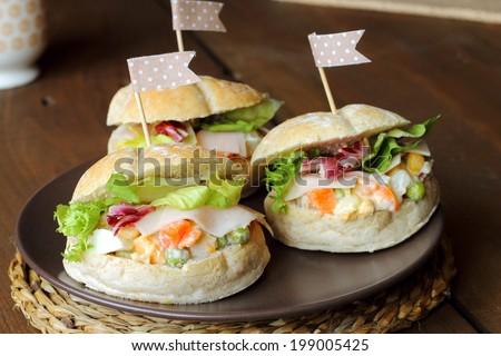 Prosciutto and russian salad sandwiches - stock photo