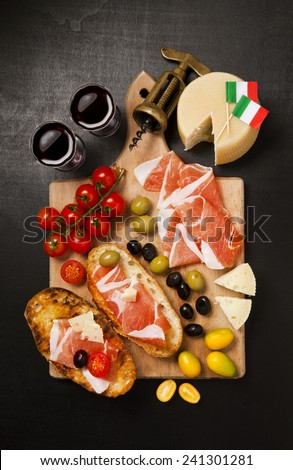 prosciutto,  cheese parmesan, olives, cherry tomatoes, red wine on wooden board. rustic snack - stock photo