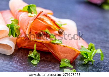 Prosciutto. Curled Slices of Delicious Prosciutto with parsley leaves on granite board. Prosciuto with spice cherry tomatoes garlic and olive. Italian and Mediterranean cuisine  - stock photo