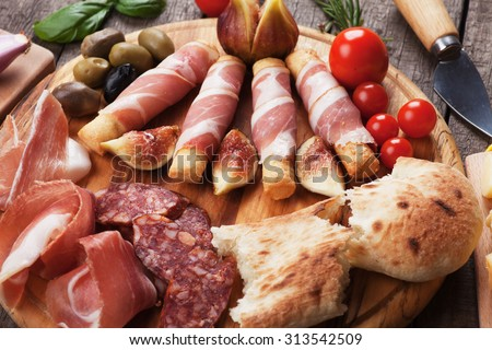Prosciutto di Parma and other italian food on wooden table - stock photo