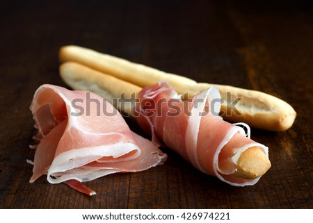 Prosciutto ham and grissini bread sticks. Isolated on dark wood.