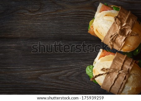 Prosciutto ham sandwiches with salad on a wooden background with copy space for text. - stock photo