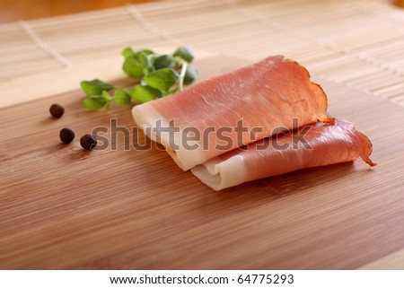 Prosciutto, italian cured ham with pepper and marjoram - stock photo