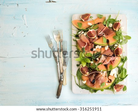 Prosciutto, melon, fig and soft cheese salad on a white serving board over grunge background, top view, copy space - stock photo