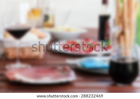 Prosciutto, red wine, mozzarella an tomatoes served on wooden table at balcony. Post processed with blur filter. - stock photo