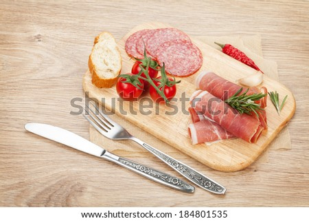 Prosciutto, salami, bread, vegetables and spices. Over wooden table background - stock photo
