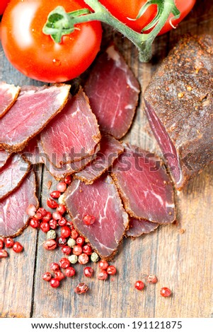 Prosciutto slices, pepper corn and tomatoes on wooden table