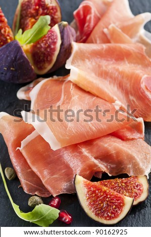 Prosciutto with fig on a black plate - stock photo