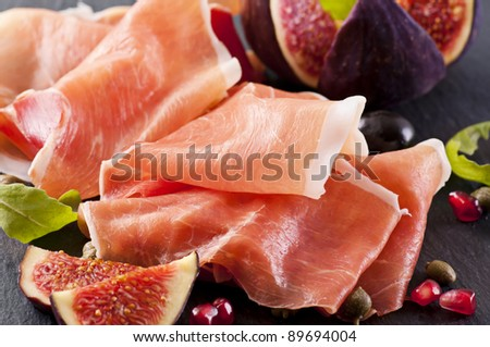 Prosciutto with figs on a black plate - stock photo