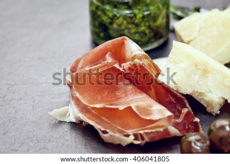 Prosciutto with pesto and Parmesan on stone table - close up