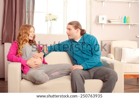 Prospective caucasian parents on the couch both touching woman's belly in living room - stock photo