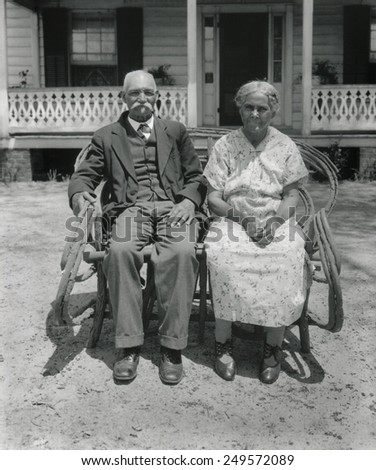 Prosperous African American farm couple, Nansemond, Virginia, May 1932. They are seated in front of a tidy house with unworn clothing. Photo by George Ackerman. - stock photo