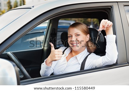 prosperous young woman holding car key and showing thumbs up - stock photo